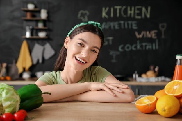 Mooie jonge vrouw met verse producten in de keuken