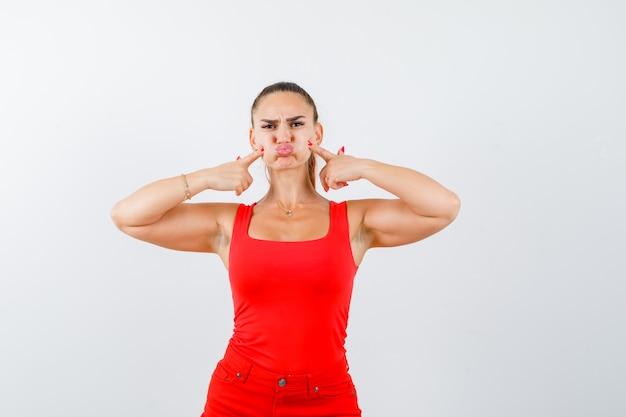 Mooie jonge vrouw met vingers op gezwollen wangen in rood mouwloos onderhemd, broek en op zoek somber, vooraanzicht.