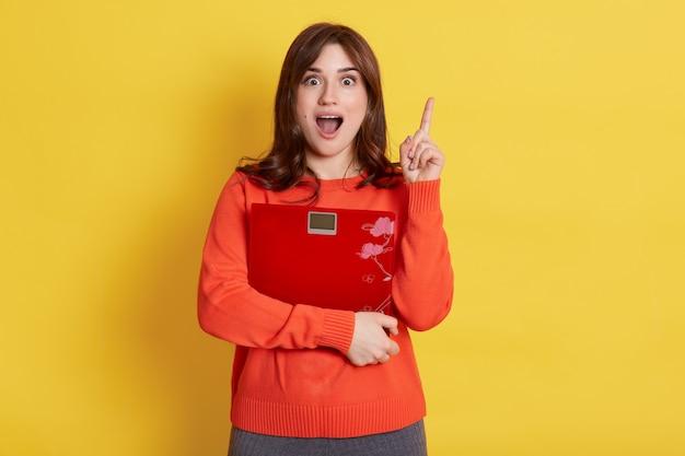 Mooie jonge vrouw met vloerweegschaal in handen, mond wijd open, wijzende vinger omhoog, met een geweldig idee hoe af te vallen, geïsoleerd over gele muur.