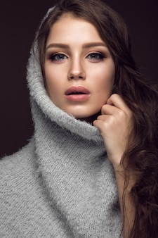 Mooie jonge vrouw met zachte make-up in warme trui en lang steil haar