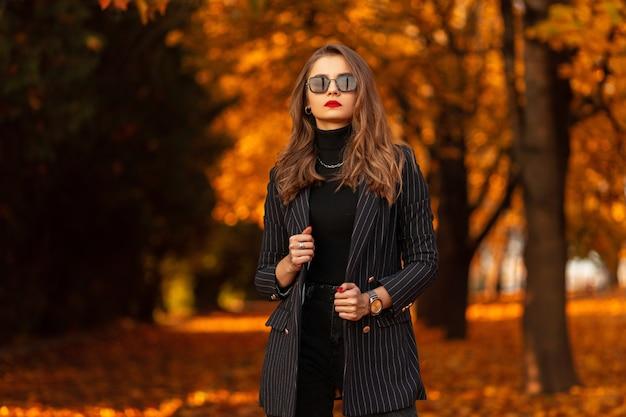 Mooie jonge vrouw met zonnebril in modieuze zakelijke kleding met een blazer en een trui loopt in het park met kleurrijke herfstbladeren. vrouwelijke zakelijke stijl en schoonheid