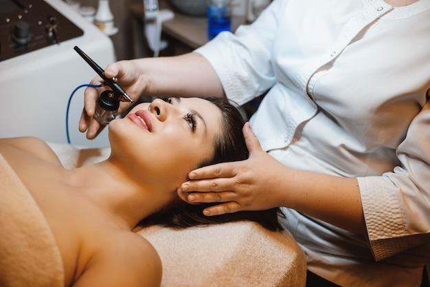 Mooie jonge vrouw met zuurstoftherapie op haar gezicht door een schoonheidsspecialist in een wellnesscentrum.