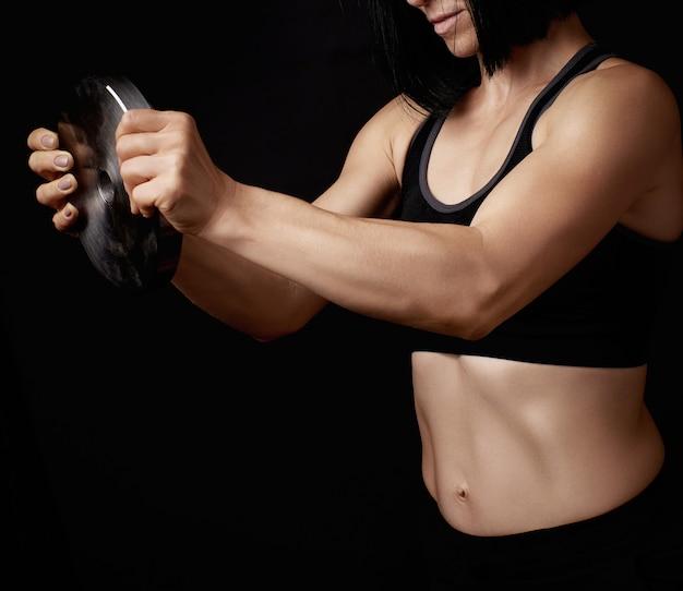 Mooie jonge vrouw met zwart haar en een sportfiguur heeft een stalen cirkel voor sport