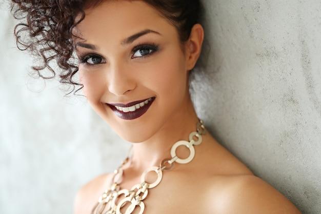 Mooie jonge vrouw met zwart krullend haar en zwarte glanzende jurk