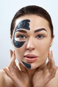 Mooie jonge vrouw met zwart masker van klei op vers gezicht. gezichtsbehandeling . cosmetologie, schoonheid en spa. huidsverzorging. meisjesmodel met kosmetisch vochtinbrengend masker.