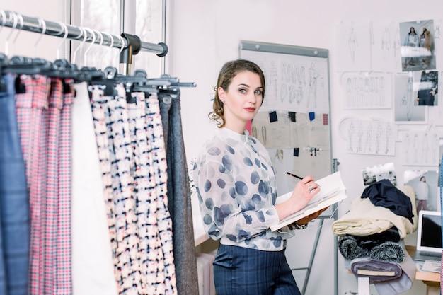Mooie jonge vrouw modeontwerper werkt aan nieuwe collectie damesbroeken voor klanten in gezellige werkplaatsstudio, naaister, kleermaker die zich in de buurt van kledingrek met modieuze stijlvolle handgemaakte broek bevindt