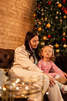 Mooie jonge vrouw moeder met haar dochter kind zitten op de bank in de buurt van de kerstboom met verlichting. fijne winter familievakanties en nieuwjaar