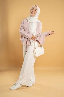 Mooie jonge vrouw moslim aziatische, op een lichte geïsoleerde achtergrond, gekleed in de moderne hijab-stijl