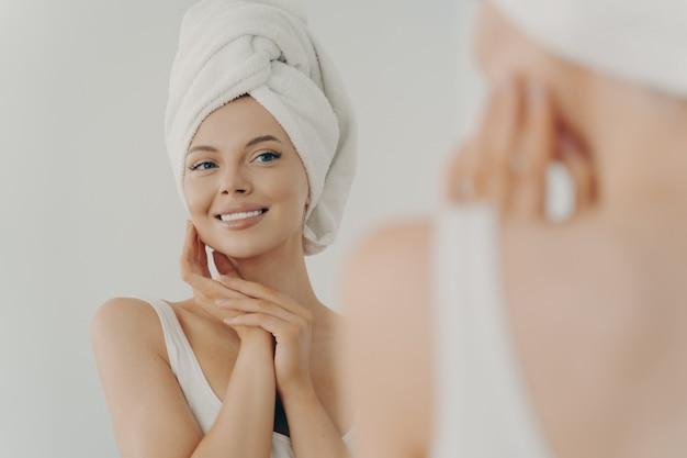 Mooie jonge vrouw na het douchen in de spiegel in de badkamer kijken