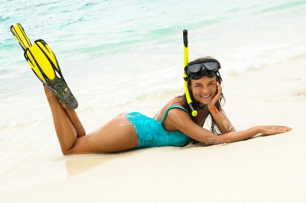 Mooie jonge vrouw na het snorkelen op het strand