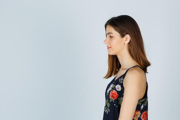Mooie jonge vrouw naar beneden te kijken in blouse en hoopvol kijkt.