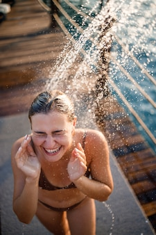 Mooie jonge vrouw neemt een ontspannende douche in een zwembroek op een zonnige dag buiten aan zee. het meisje op vakantie rust. selectieve focus