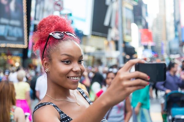 Mooie jonge vrouw nemen selfie times square