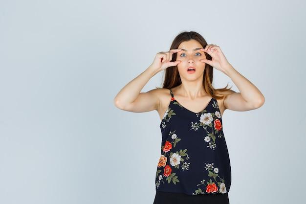 Mooie jonge vrouw ogen openen met vingers in blouse en geschokt kijken