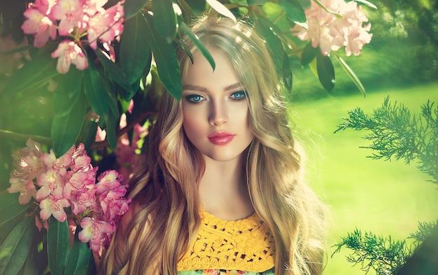 Mooie jonge vrouw omringd door bloeiende bloembomen zachte make-up roze lippenstift en vrij liggende krullen 0f lang haar lentestijl lentebloesem en bloei van de jeugd