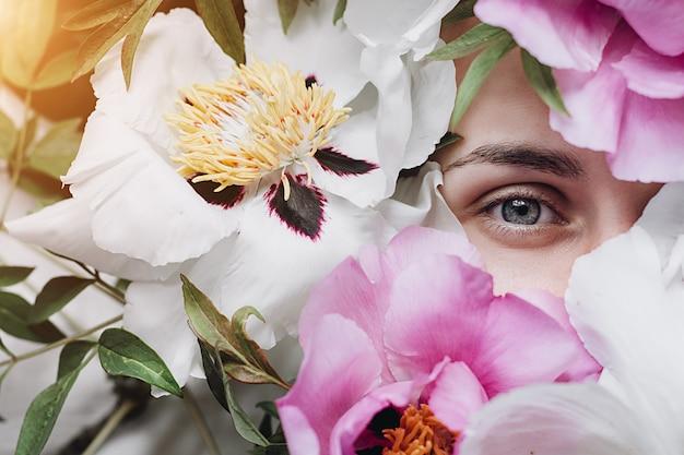 Mooie jonge vrouw omringd door pioenrozen bloemen zomer. mooi donkerbruin jong meisje dat van bloemen geniet. cover idee stemming