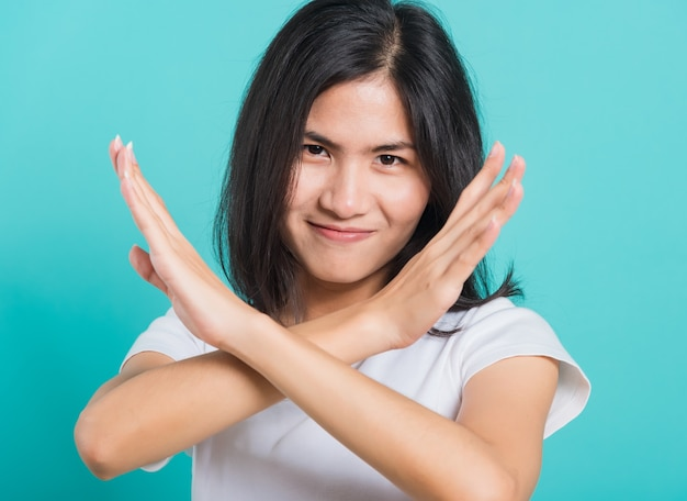 Mooie jonge vrouw ongelukkig of zelfverzekerd met twee kruisende armen zegt nee x-teken