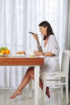 Mooie jonge vrouw ontbijten en lachen tijdens het luisteren naar audiobericht van vriend