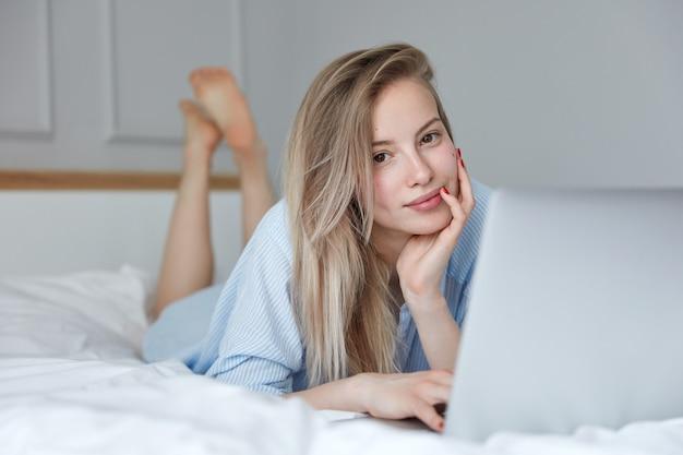 Mooie jonge vrouw ontspannen in bed met laptop