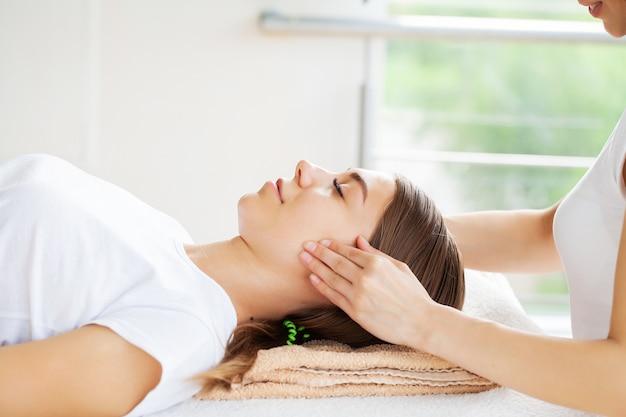 Mooie jonge vrouw ontspannen met handmassage in beauty spa salon