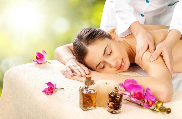 Mooie jonge vrouw ontspannen met handmassage in beauty spa
