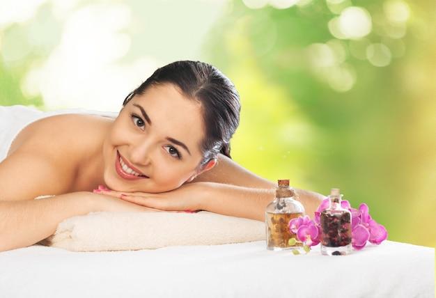 Mooie jonge vrouw ontspannen met massage in beauty spa
