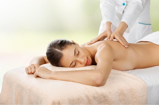 Mooie jonge vrouw ontspannen met massage in beauty spa Premium Foto