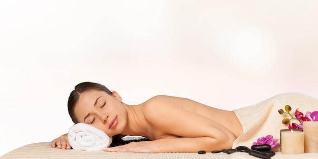 Mooie jonge vrouw ontspannen met stenen massage in beauty spa