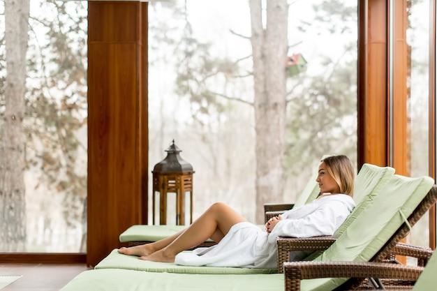 Mooie jonge vrouw ontspannen op de strandstoel bij het zwembad in de spa