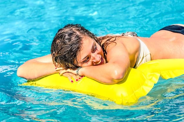 Mooie jonge vrouw ontspannen op een gele opblaasbare matras in helder blauw water - zomer chillen met meisje in zwembad in exclusief hotelresort