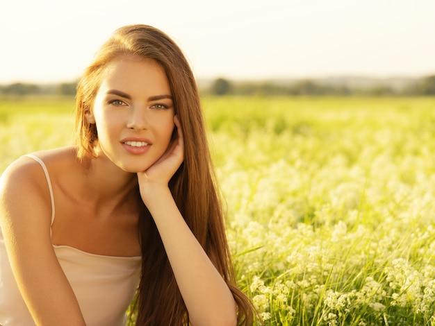 Mooie jonge vrouw op aard over de achtergrond van een veld zomer.