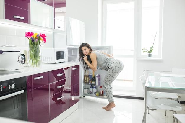 Mooie jonge vrouw op de nieuwe keuken. violette keuken. aantrekkelijk wijfje bij de ochtendkoffie.