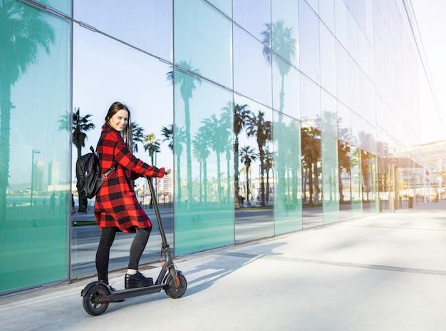 Mooie jonge vrouw op een elektrische scooter met een rugzak. eco-vriendelijk concept