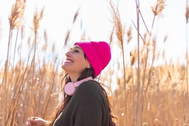 Mooie jonge vrouw op een gebied van hoog gras luisteren muziek