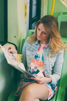 Mooie jonge vrouw op een tram / tram op zoek op een kaart, tijdens haar toeristische reis