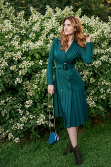 Mooie jonge vrouw op een wandeling in een groene jurk.