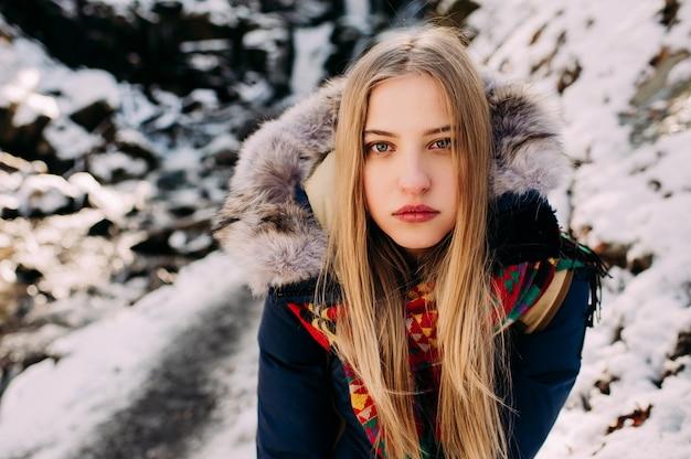 Mooie jonge vrouw op een wandeling in een winter bos