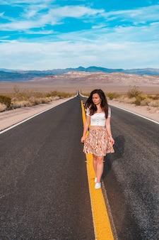 Mooie jonge vrouw op een weg met gele rijstroken in het midden van death valley, vs