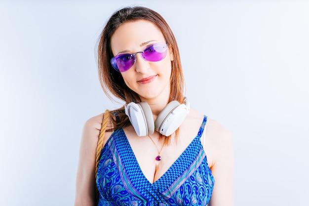 Mooie jonge vrouw op een witte achtergrond die recht vooruit kijkt en een draadloze muziekkoptelefoon draagt