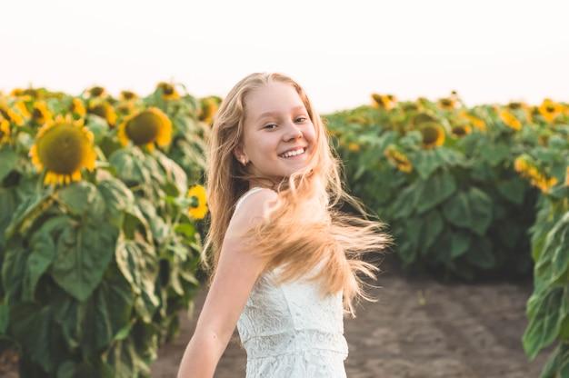Mooie jonge vrouw op een zonnebloemgebied. portret van een jonge vrouw in de zon. stuifmeelallergieën concept. levensstijl geluk buitenshuis