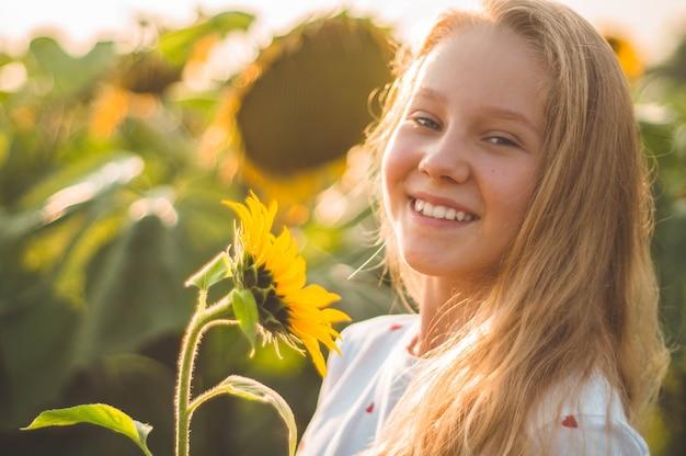 Mooie jonge vrouw op een zonnebloemgebied. portret van een jonge vrouw in de zon. stuifmeelallergieën concept