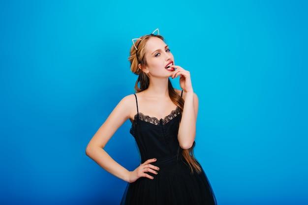 Mooie jonge vrouw op feestje, bedachtzaam kijken en vinger bijten. het dragen van een elegante zwarte jurk, een hoofdband van een kattenoor met diamanten, een manicure met goudpoets.