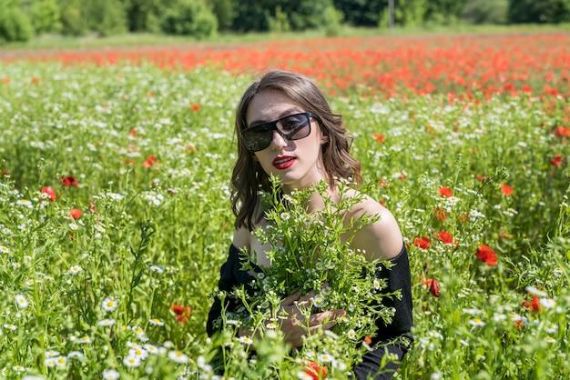 Mooie jonge vrouw op gebied van bloemen madeliefjes, genieten van de natuur