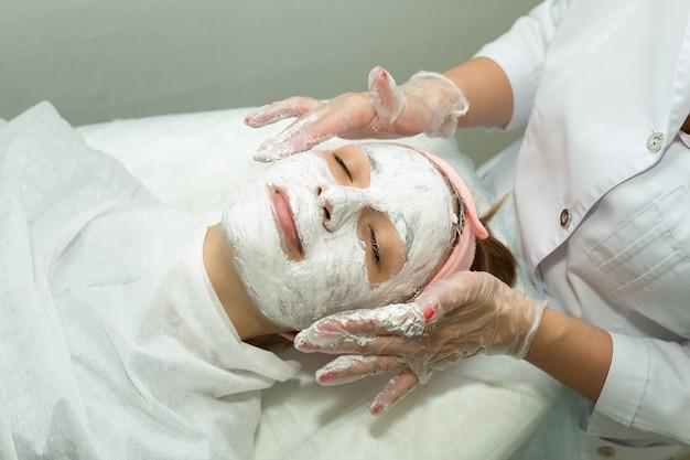 Mooie jonge vrouw op gezicht reinigingsprocedure in cosmetologie