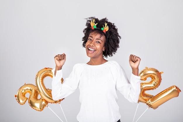 Mooie jonge vrouw op nieuwjaarsfeest over witte studioachtergrond met gouden ballons