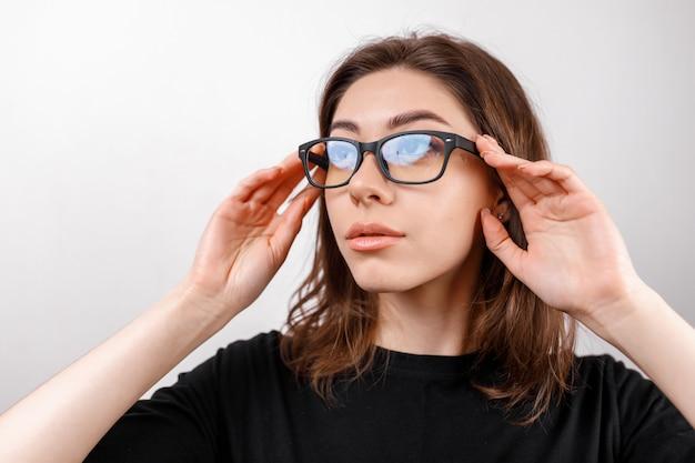 Mooie jonge vrouw op wit ziet er weg met een bril en een zwart shirt. copyspace