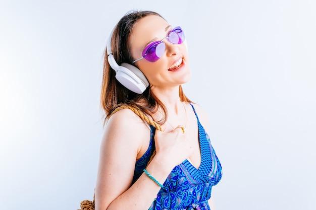Mooie jonge vrouw op witte achtergrond die draadloze muziekhoofdtelefoons draagt