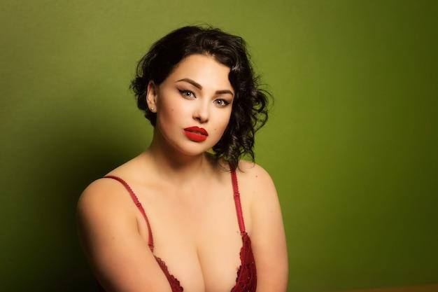 Mooie jonge vrouw plus grootte in lingerie in het interieur