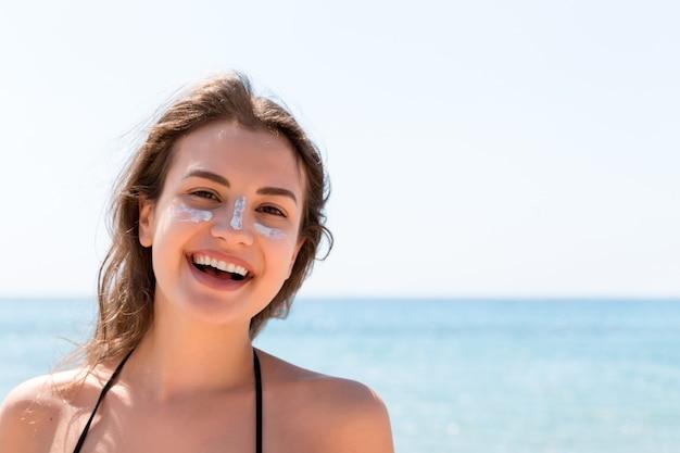 Mooie jonge vrouw poseert voor de camera met zonnebrandcrème op haar gezicht over de achtergrond van de zee.
