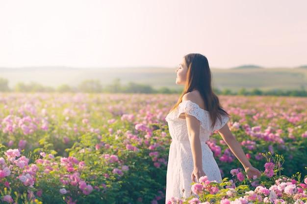 Mooie jonge vrouw poseren in de buurt van rozen in een tuin.